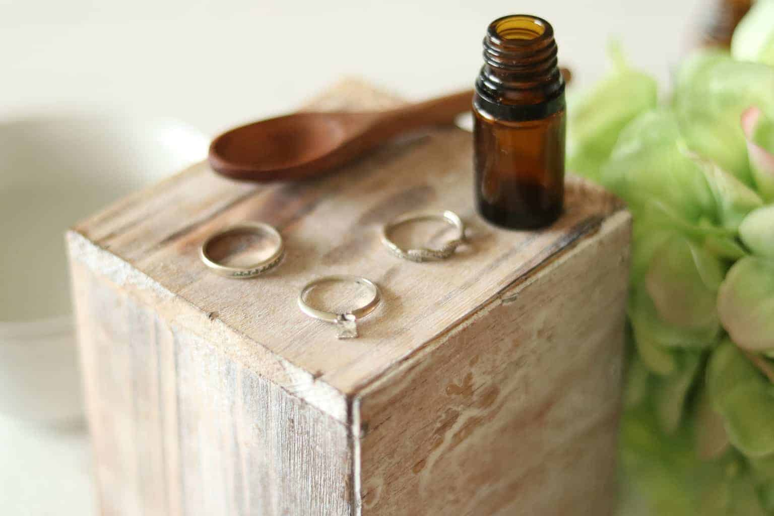 homemade jewelry cleaner in glass bottle with white gold rings, wooden spoon on wooden box