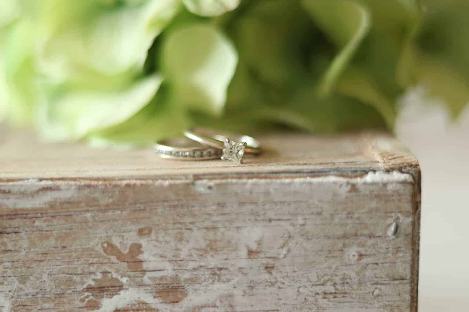 Wedding and engagement ring on old wooden box with flowers in background.