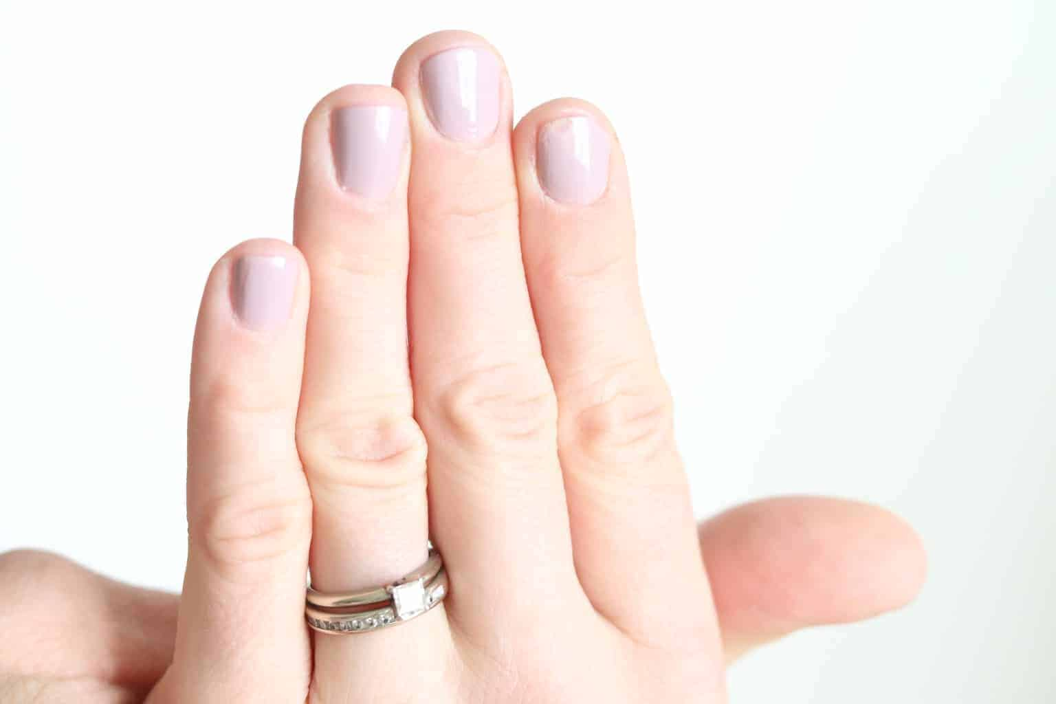 women hand with light pink nails