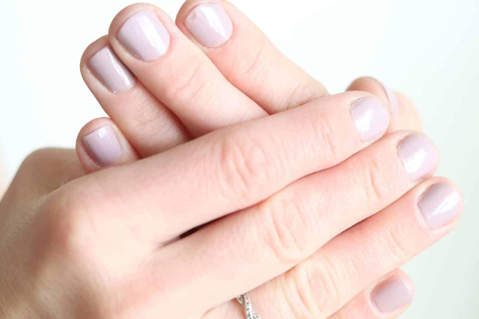 Lewomen hands with light pink painted fingernails