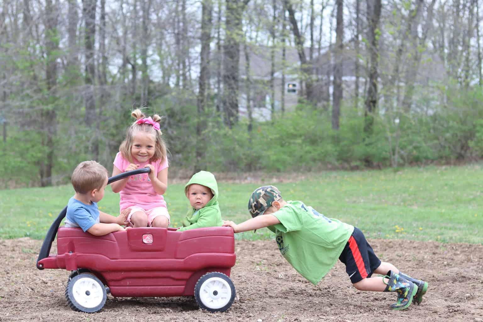 Little boy pushing kids in a wagon.