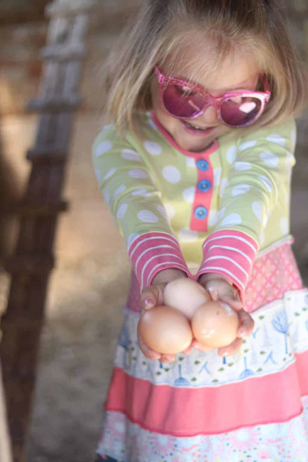 little girl in dress holding farm fresh eggs