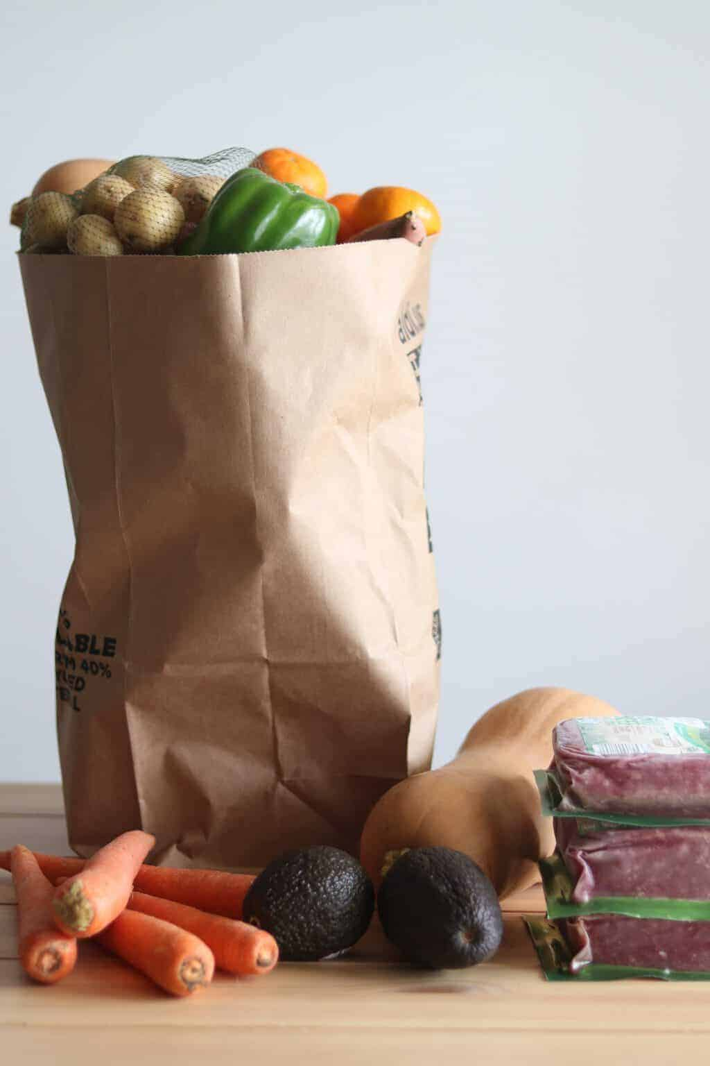 Fresh veggies and meet in brown paper shopping bag and on table.