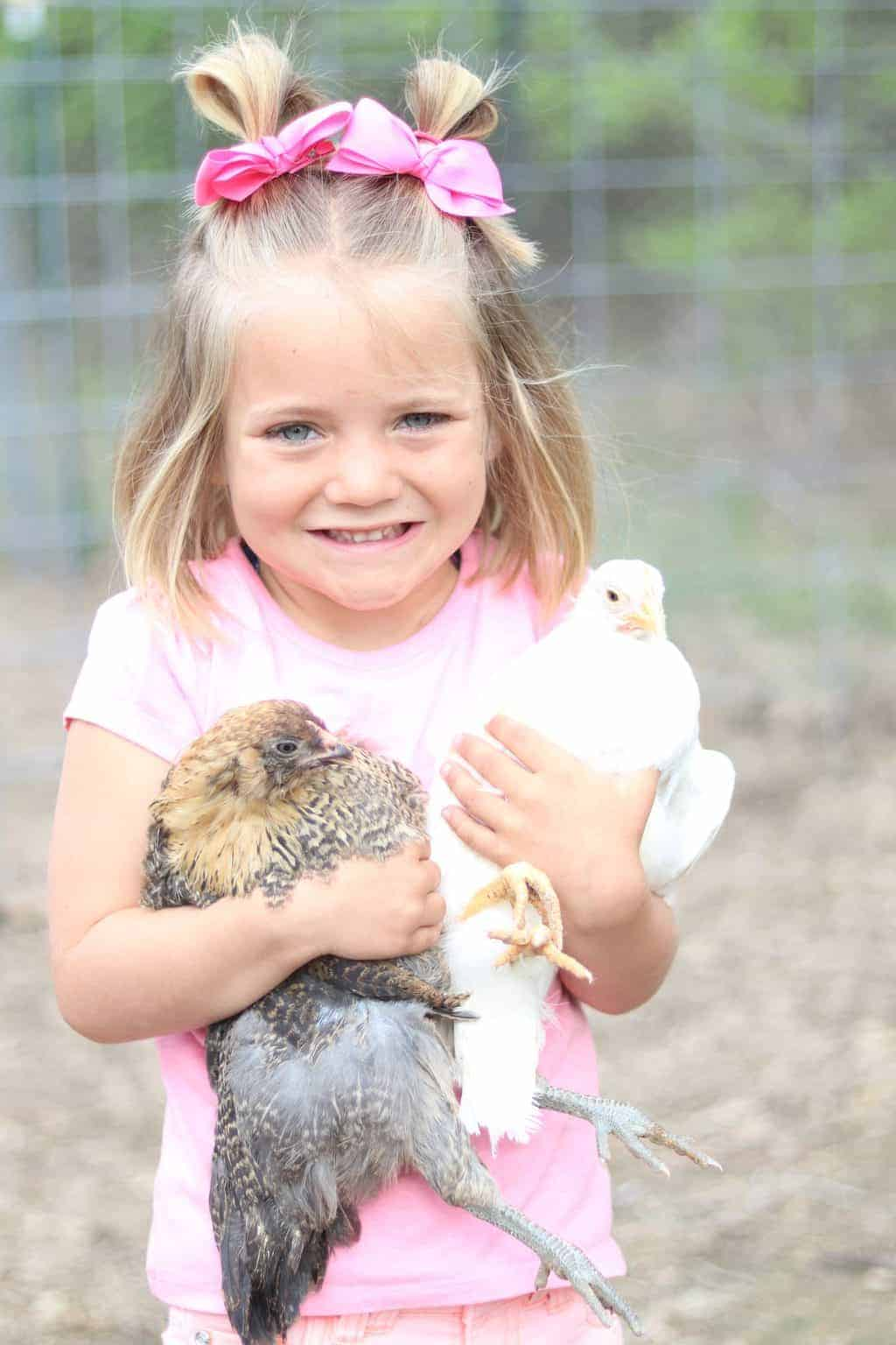 A little girl holding chickens outside.