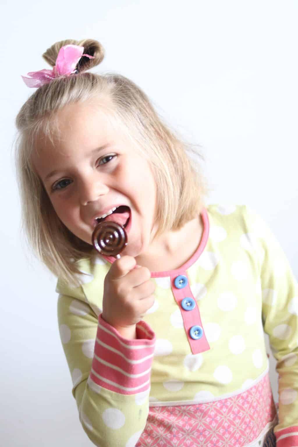 Little girl licking a healthy lollipop.