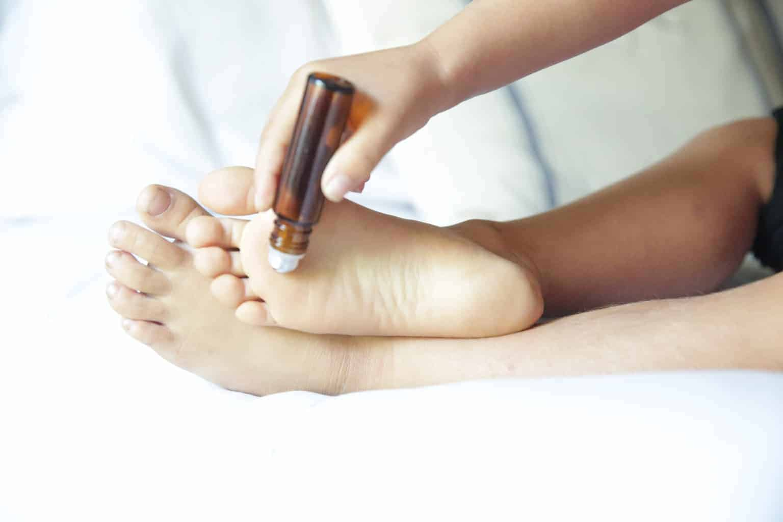applying essential oil roller bottom to foot