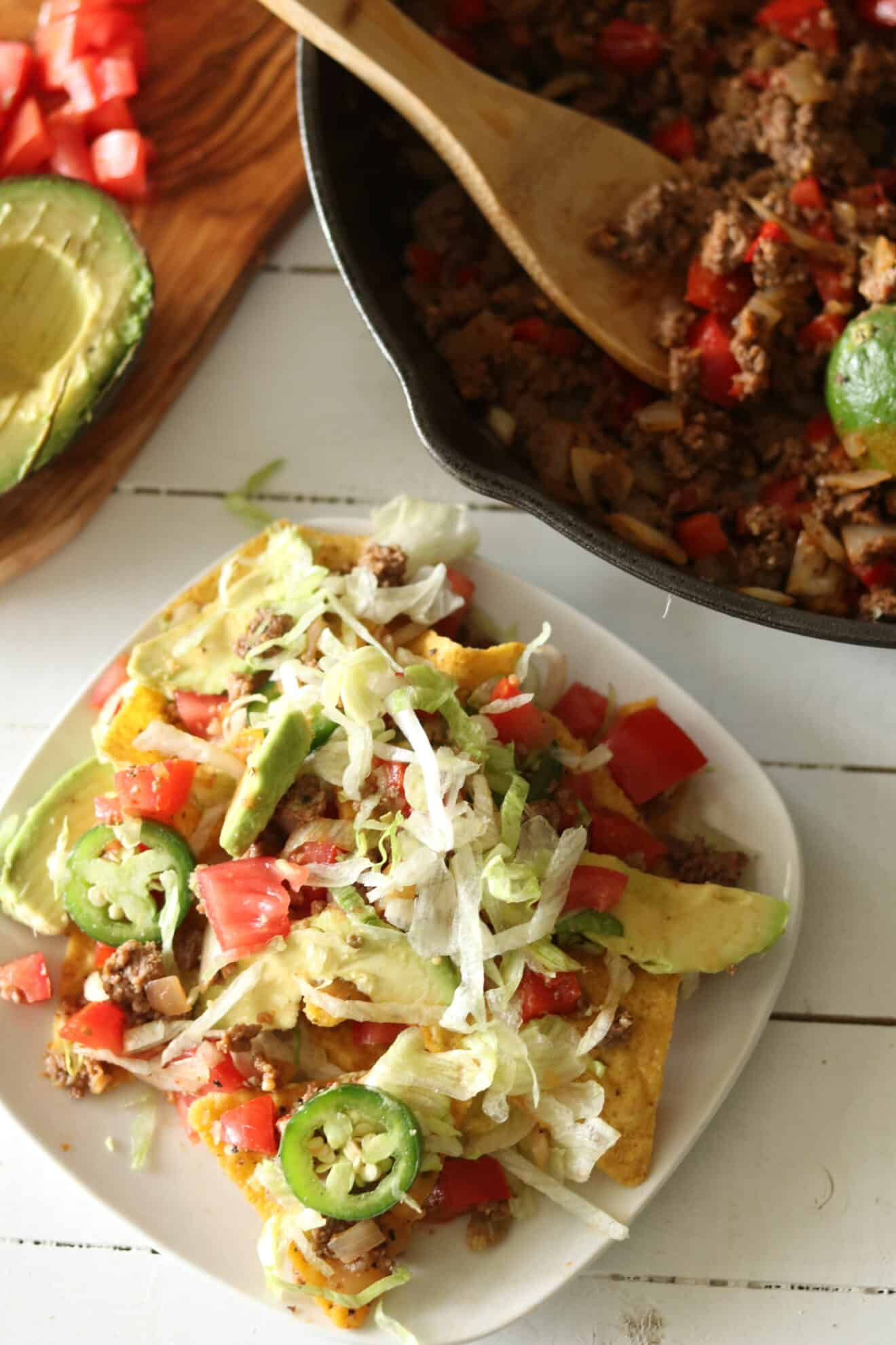 Homemade nachos topped with jalapeños, tomatoes, and avocado.