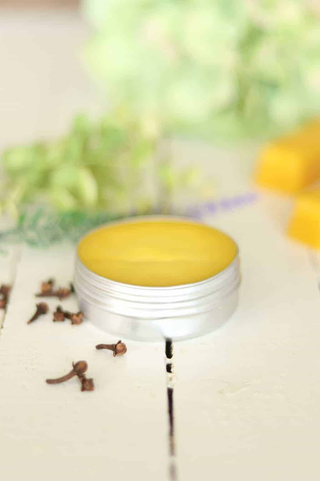 Homemade solid perfume with flowers in background.