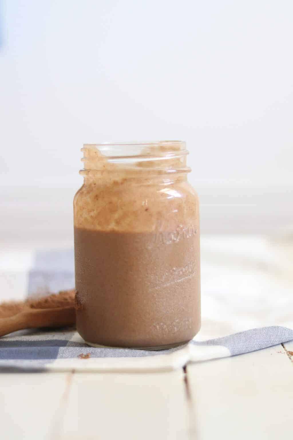 Healthy peanut butter chocolate ice cream in quart size mason jar on white shiplap.