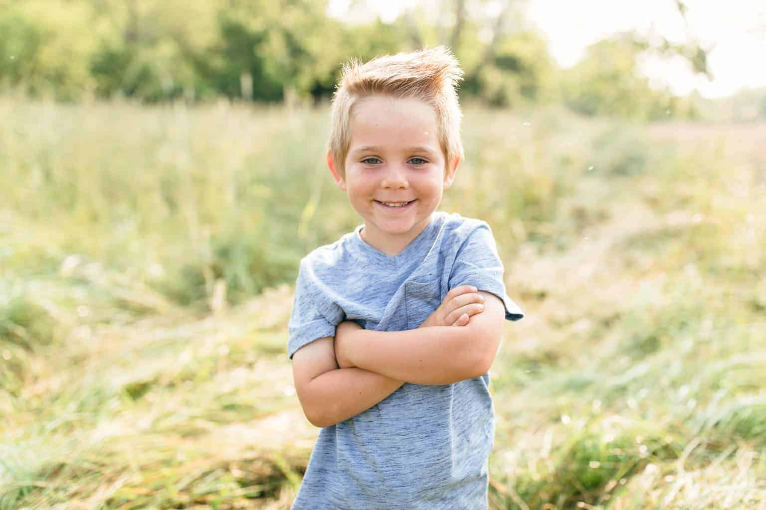 picture of little boy in blue shirt in a open field