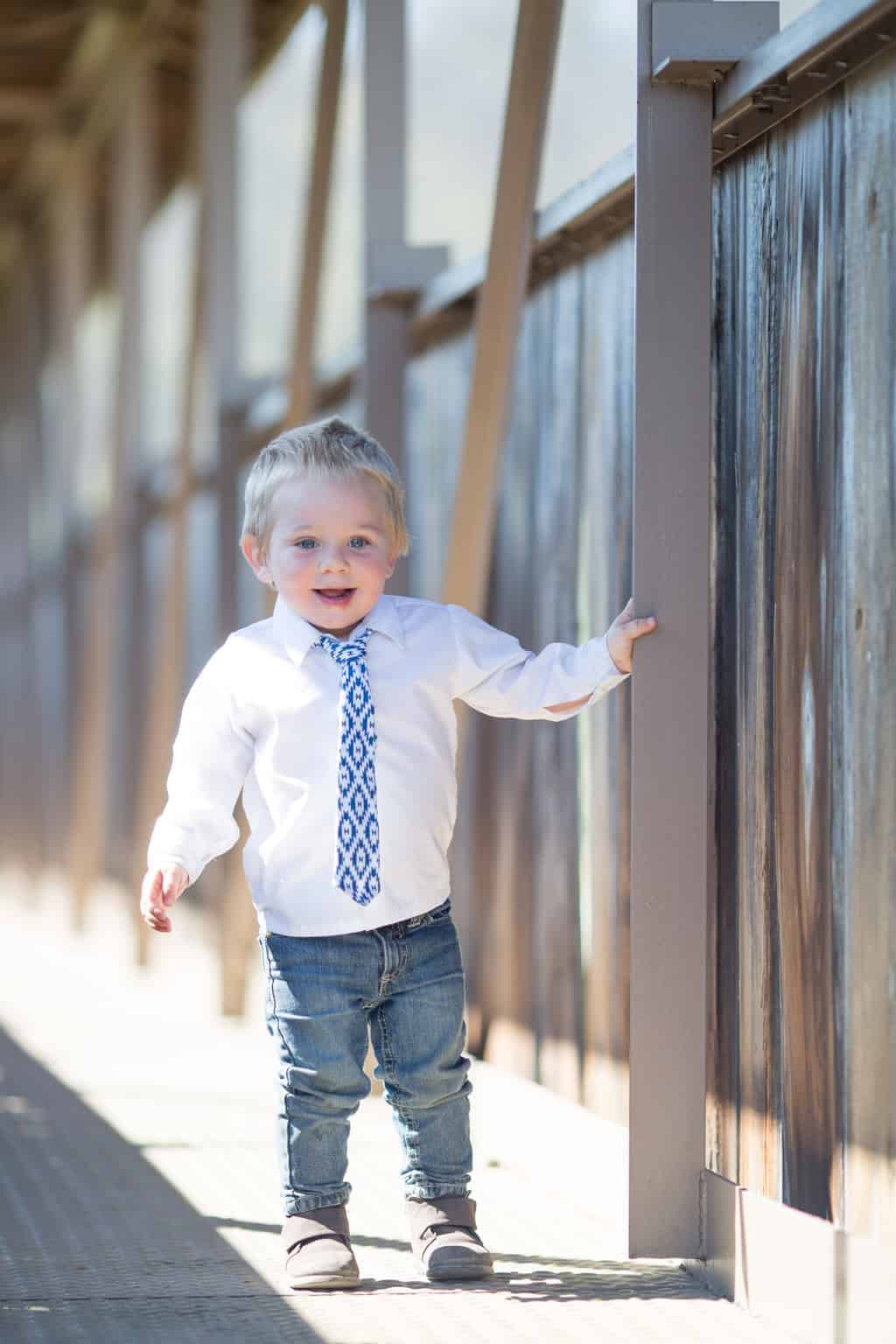 picture of toddler in white button down and blue tie standing on wood covered bridge