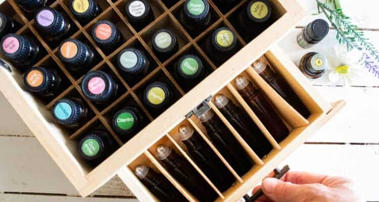 essential oils in wooden storage box on white ship lap
