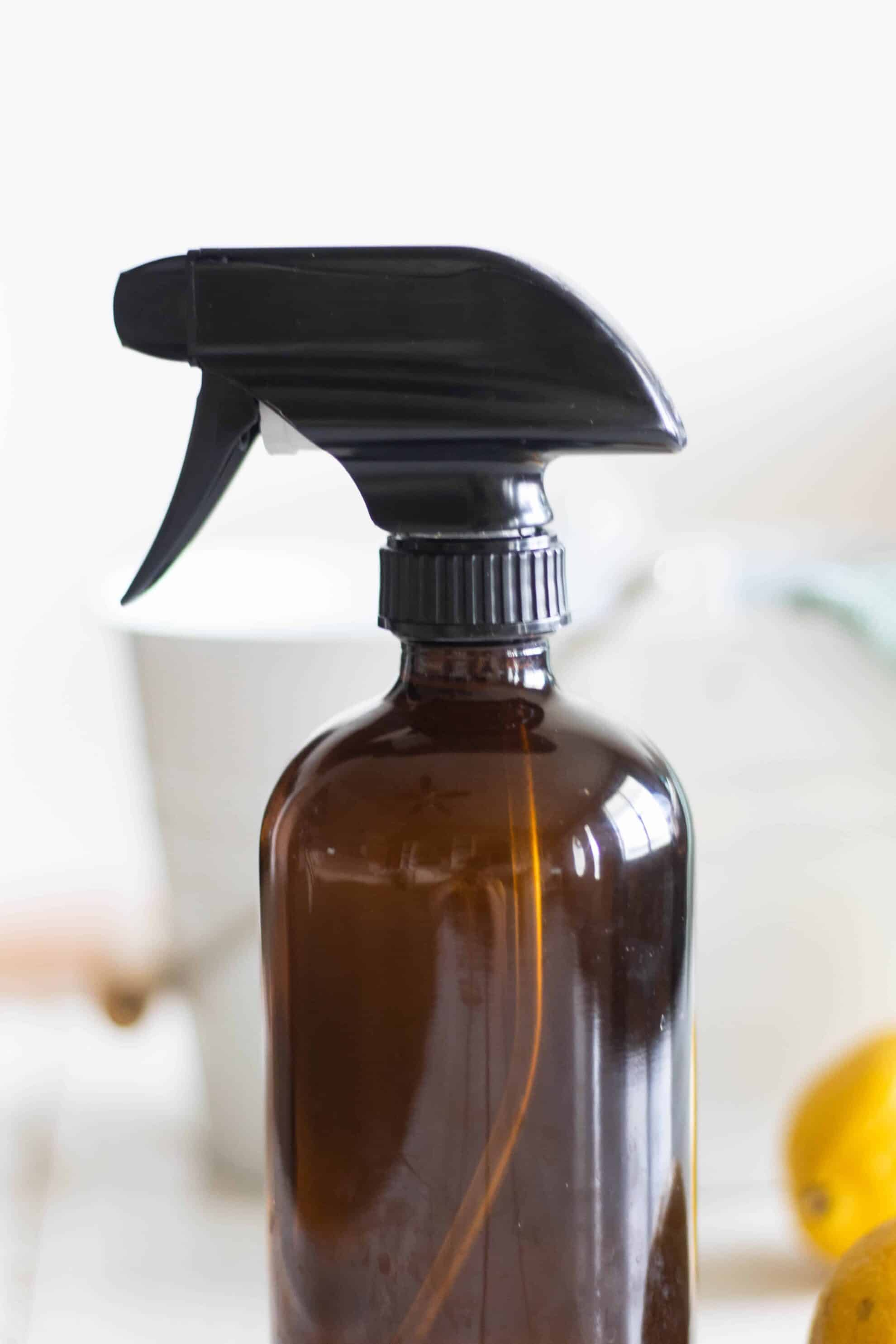 brown glass spray bottle with toxic free house cleaner on white background