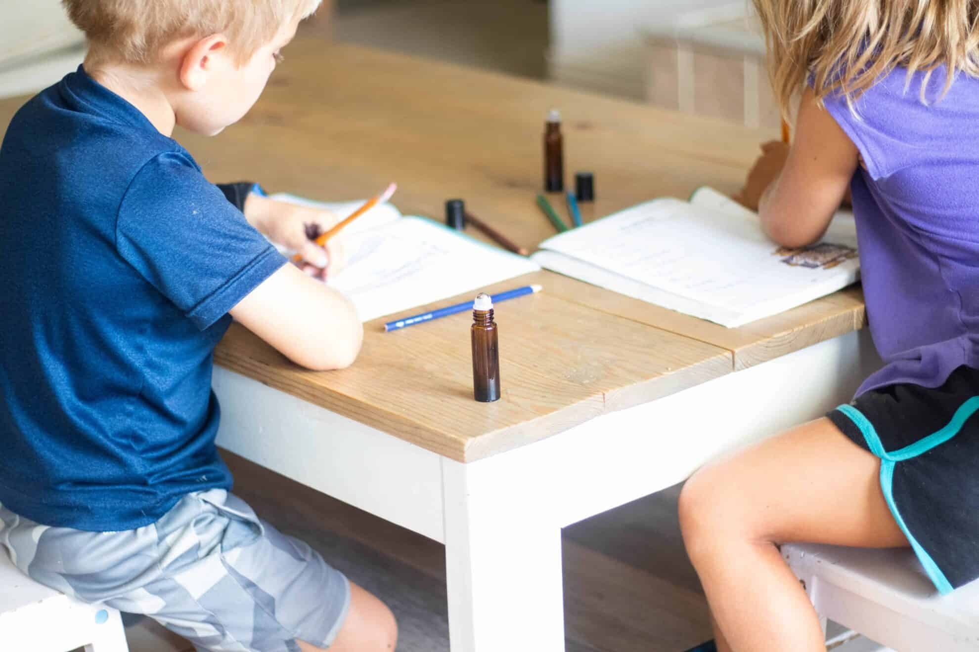 two little kids sitting at coffee table working on homework