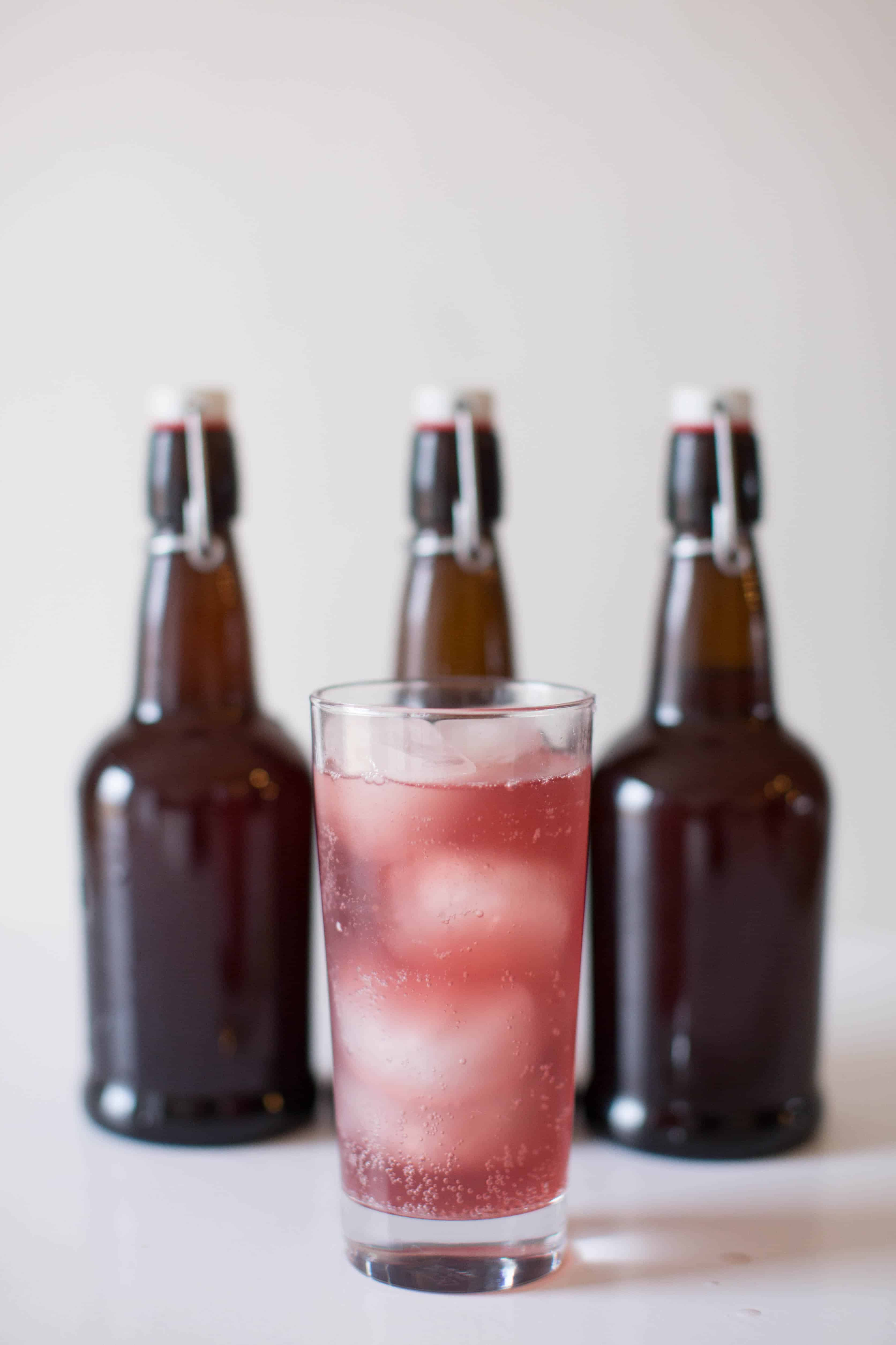 Grape water kefir in glass cup with amber flip top soda bottles in background.