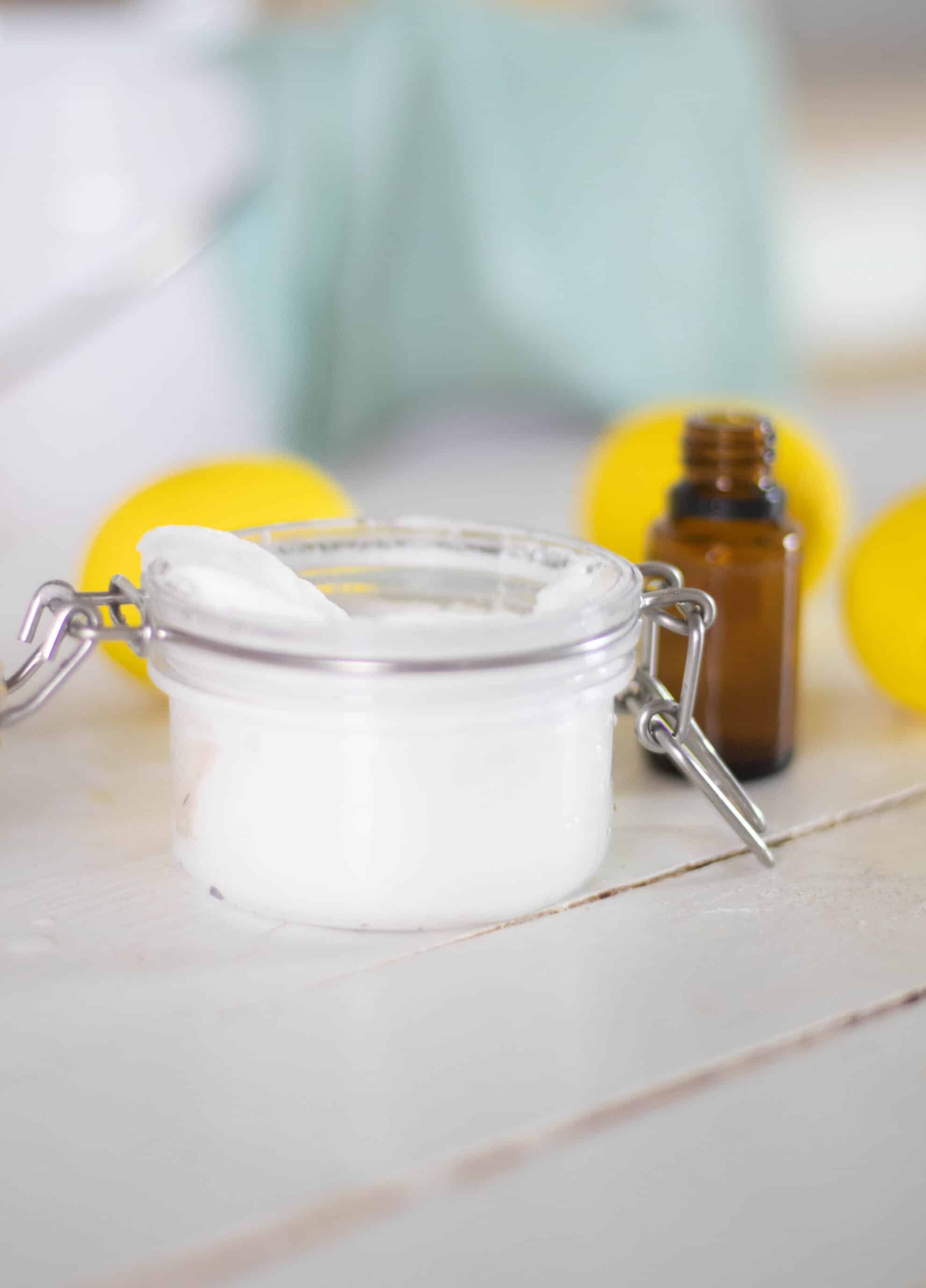 white soft scrub in glass jar on white ship lap, amber essential oil bottle and lemons in background