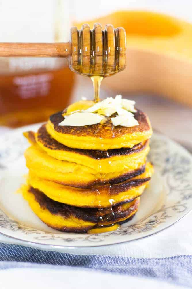 healthy pumpkin pancakes on floral plate with honey being poured over them