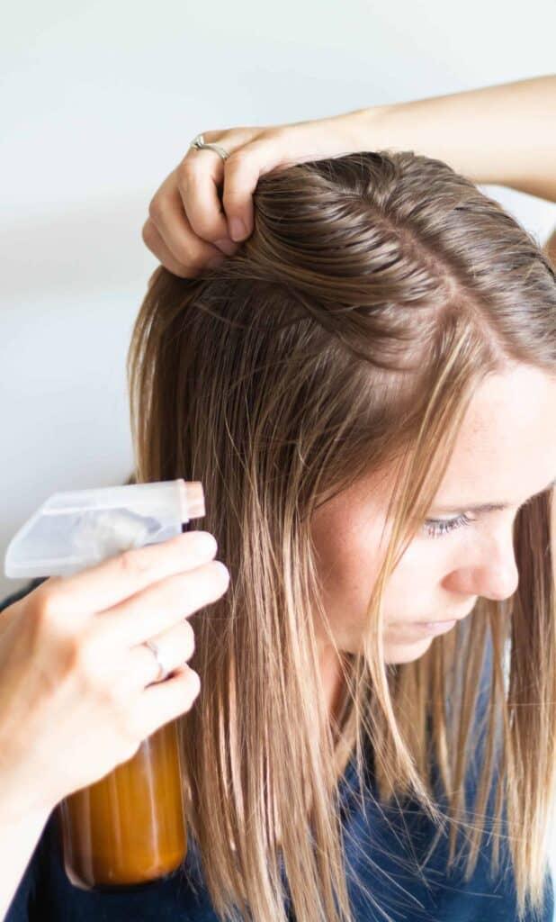 women spraying dry shampoo into her light brown hair