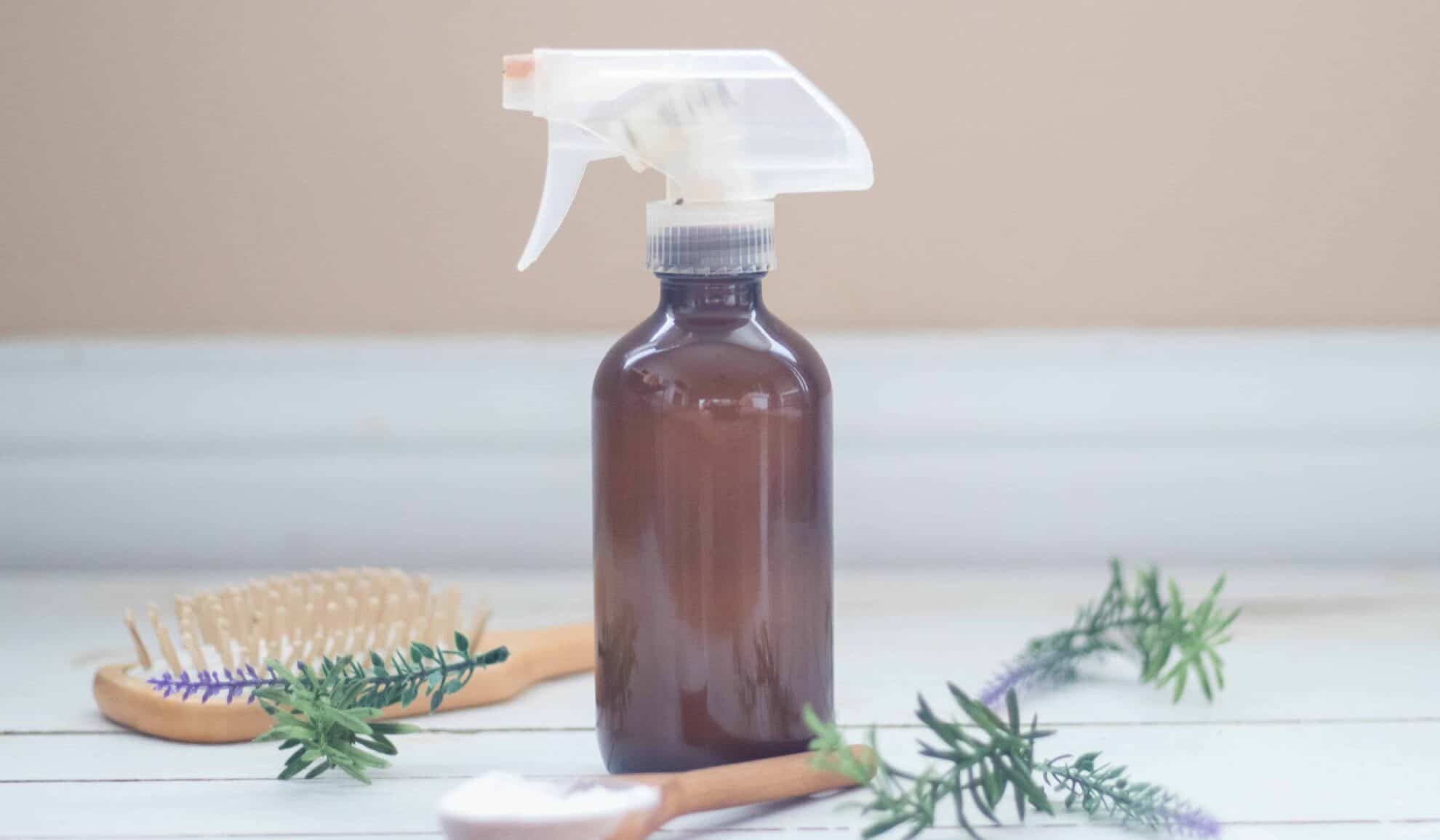 medium sized amber color glass dry shampoo spray bottle sitting on white ship lap with rosemary and lavender sprigs around