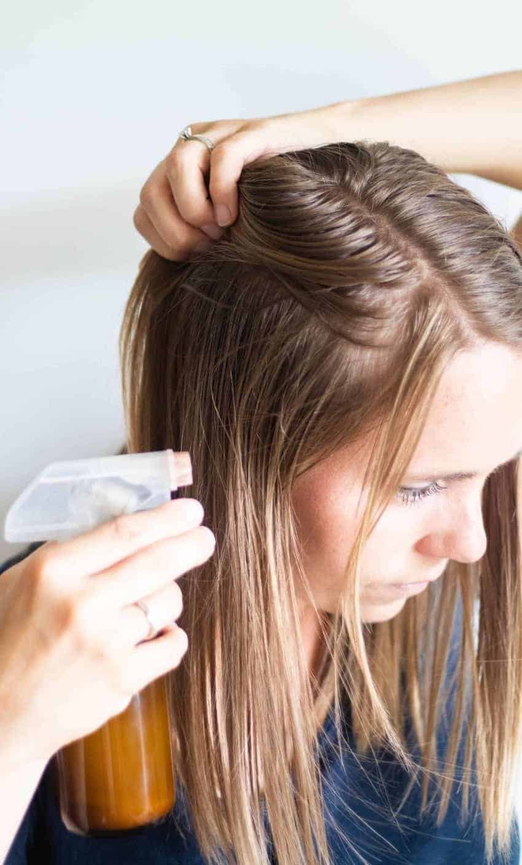 Spraying DIY dry shampoo on hair.