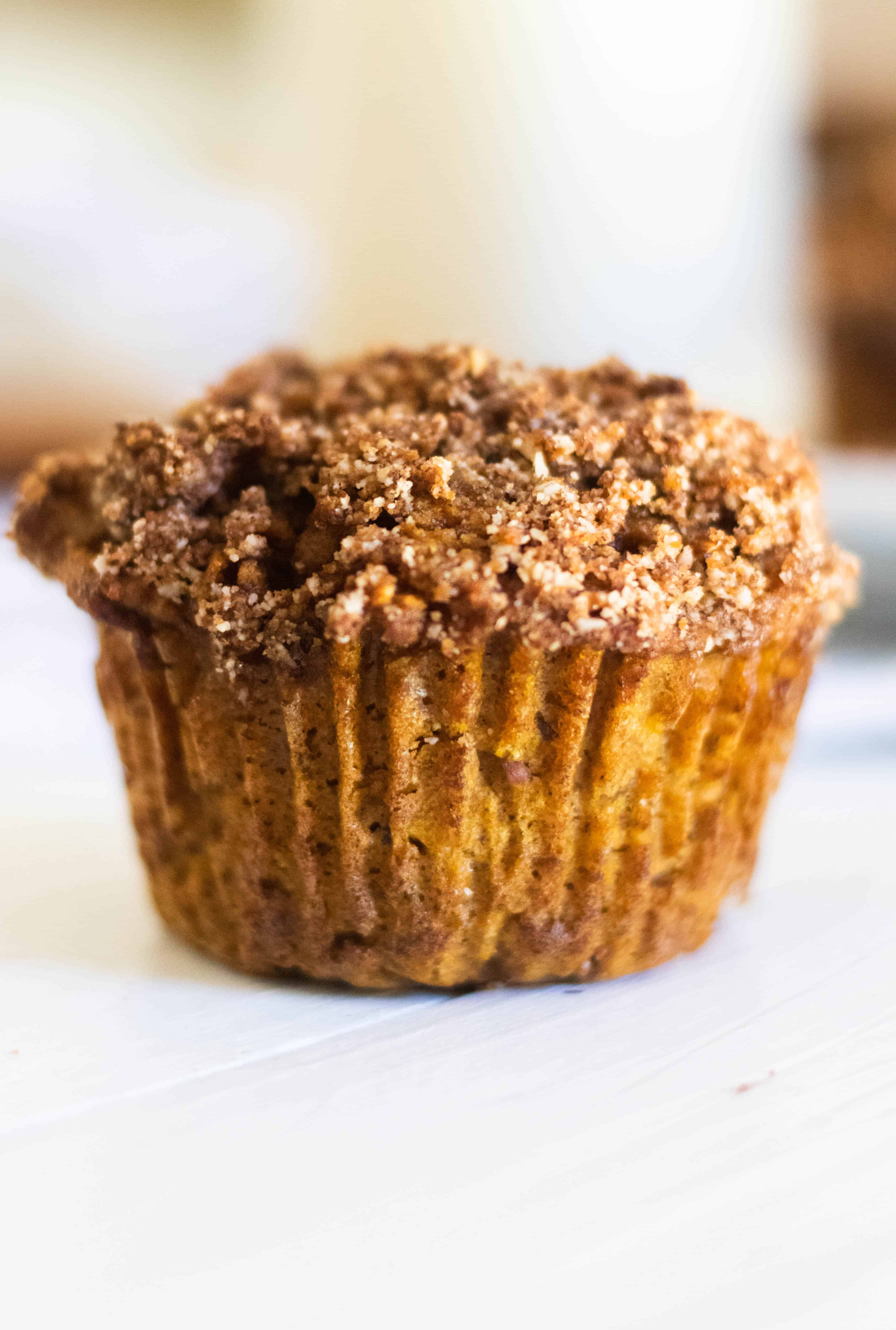 Homemade pumpkin muffin with cinnamon crumble on white table.