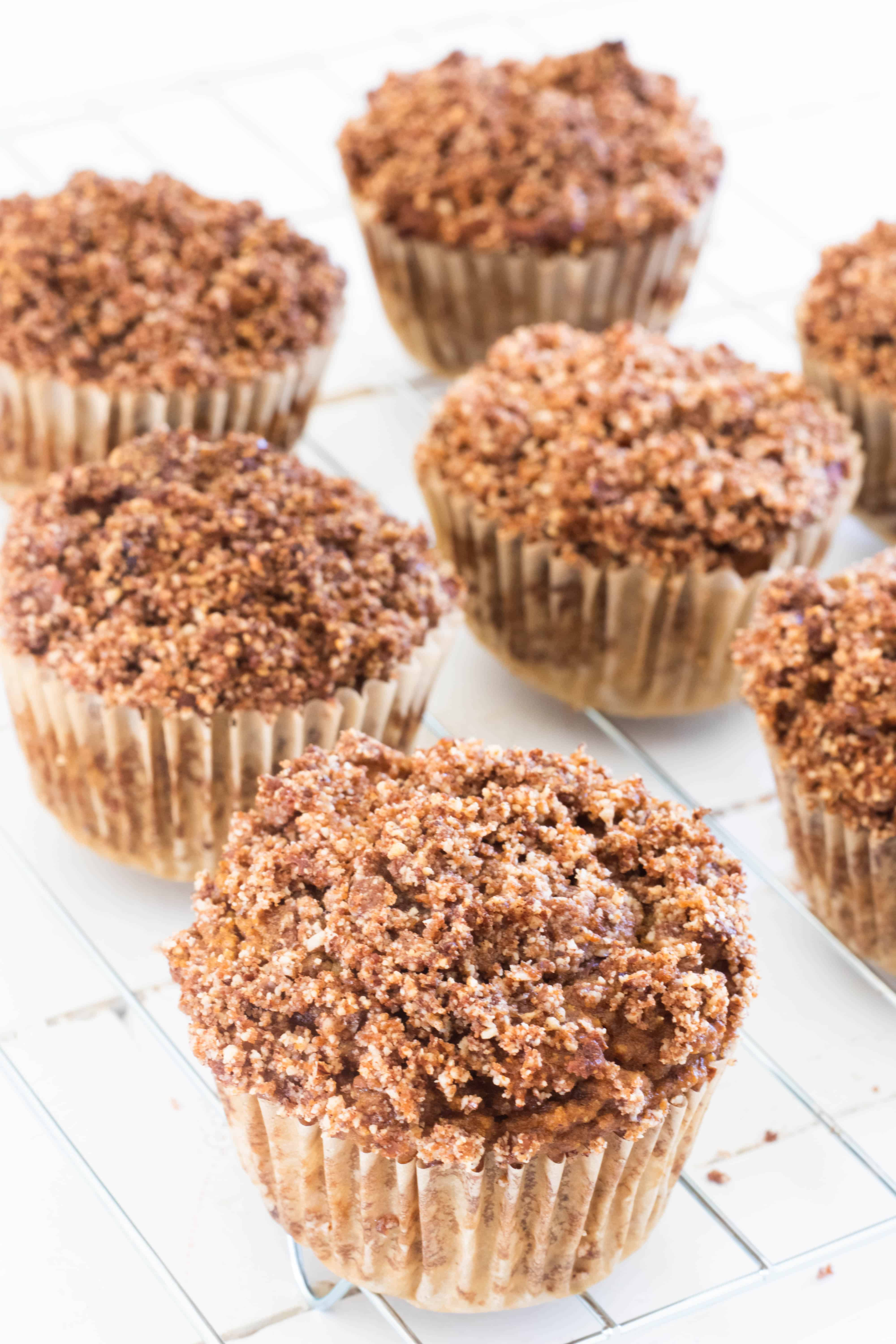 Muffins with crumble topping on drying rack on white table.