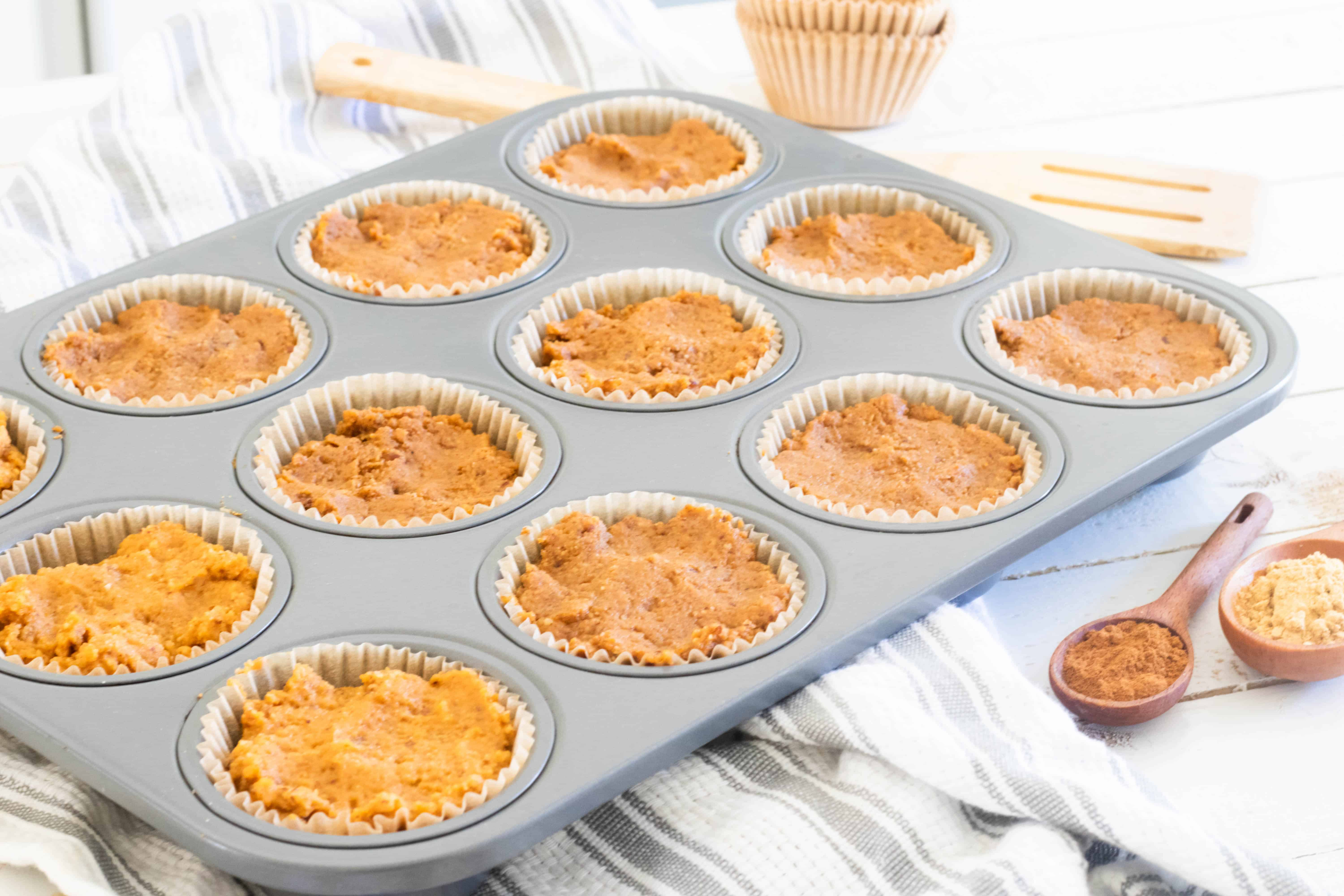 Pumpkin batter in a muffin pan on gray and white strip towel.