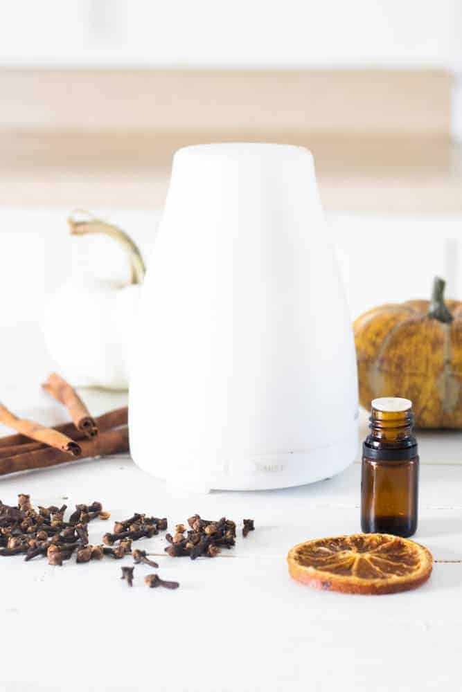 white diffuser surrounded by fall decor on white board with a fall diffuser blend essential oil