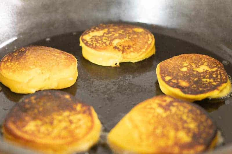 pancakes frying on cast iron skillet