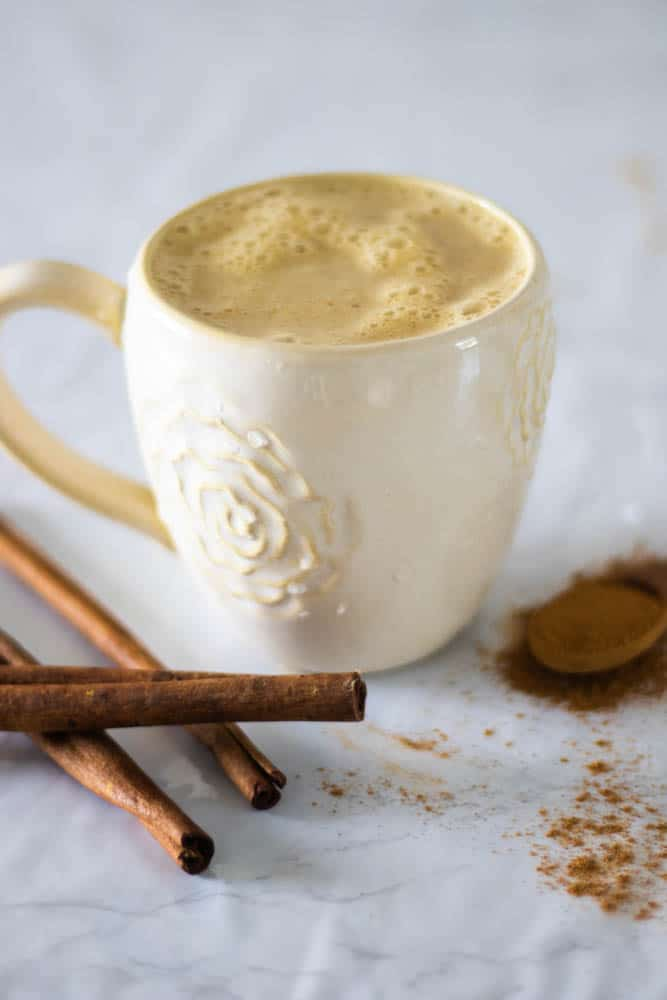 pumpkin spice latte in white mug on white table with cinnamon sticks