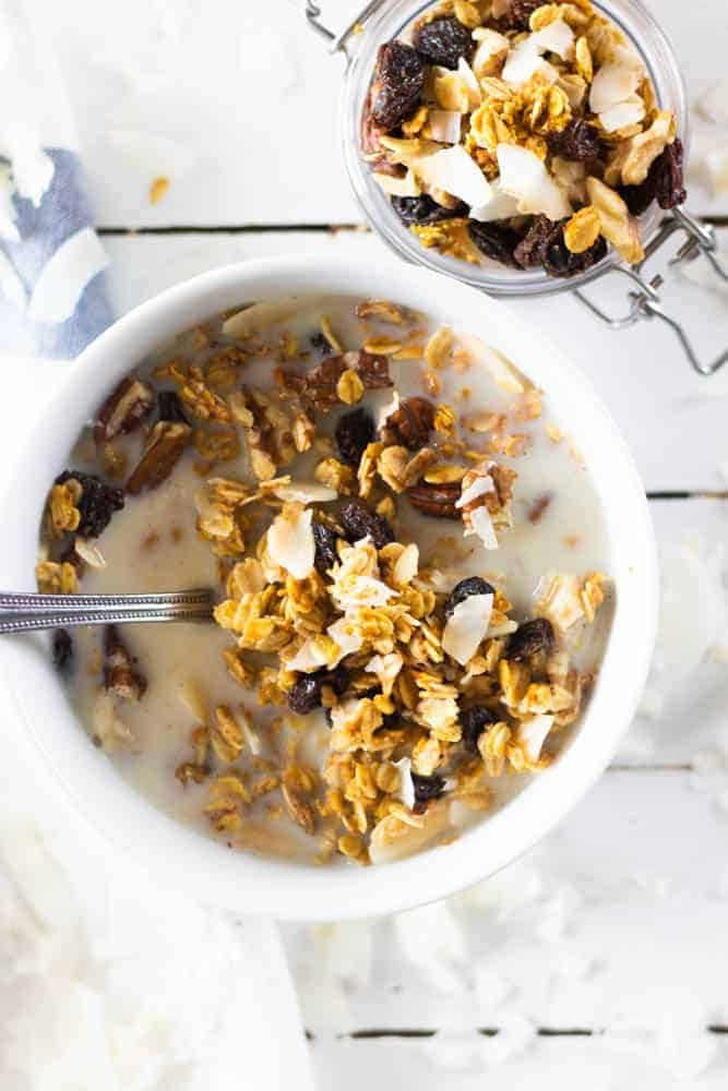 cereal in milk in white bowl and all-natural granola in small jar