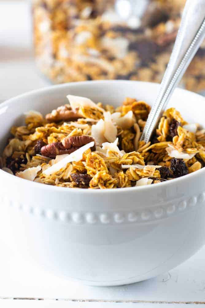 homemade pumpkin granola in white bowl with nuts and coconut chips on top