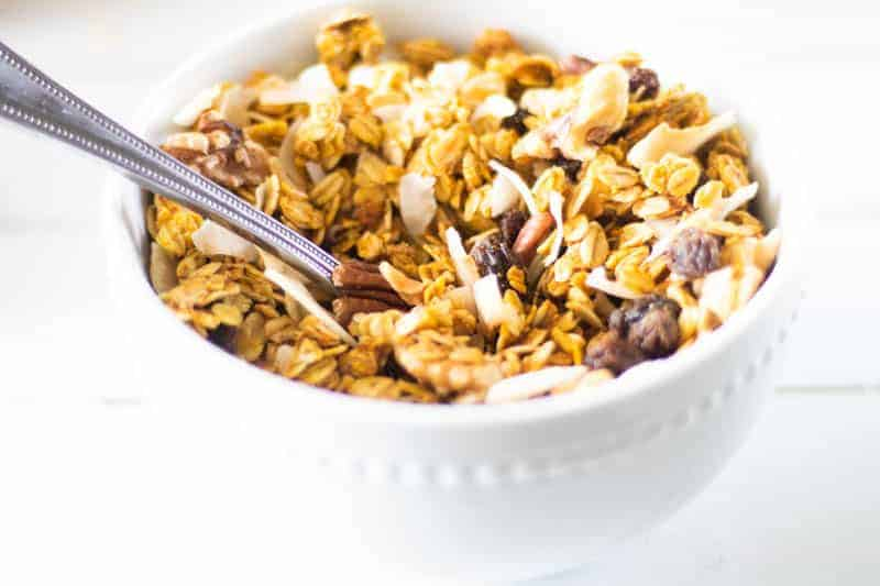 pumpkin granola in a bowl with spoon on white shiplap