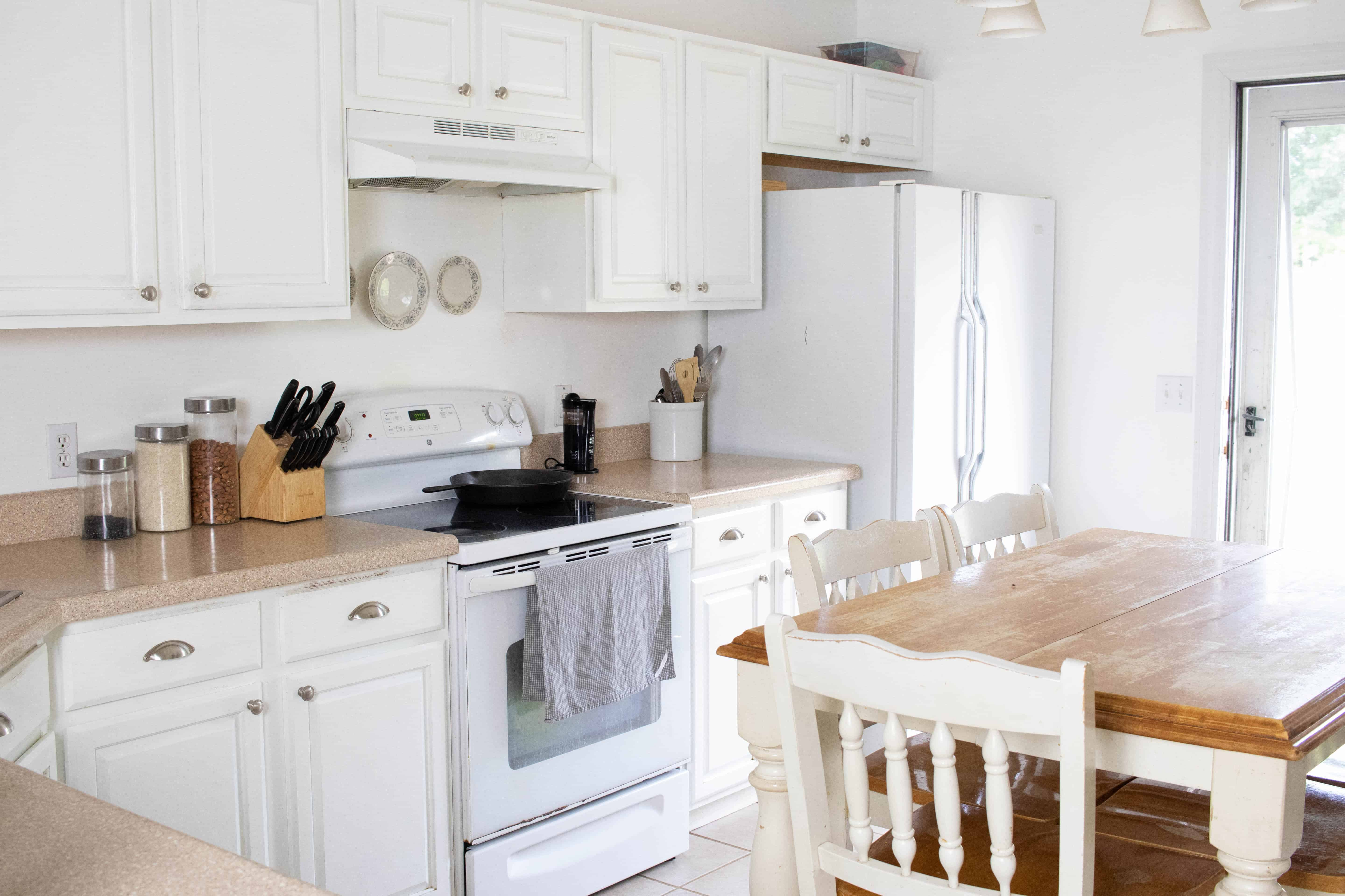 Clean organized kitchen with white cabinets, brown countertops, and white appliances.