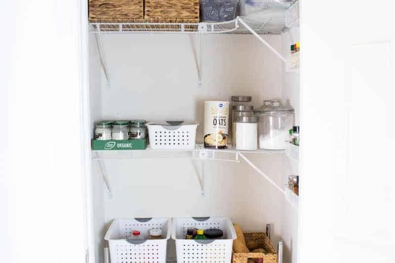 Storage containers in clean white pantry.