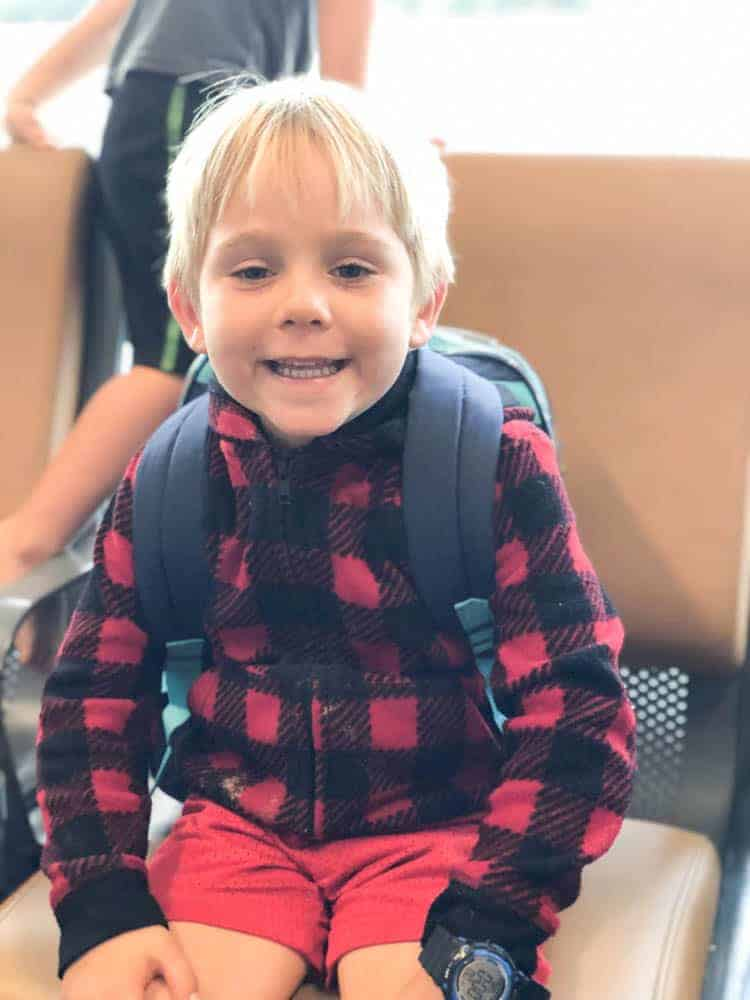 Little boy with backpack sitting in airport ready for his first time flying.