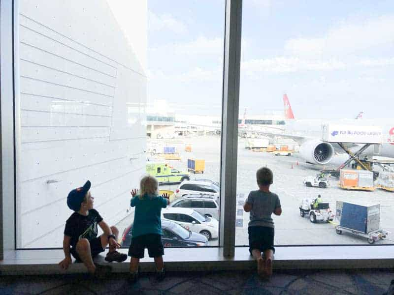 three boys looking out the window at an airport apron before their flight.