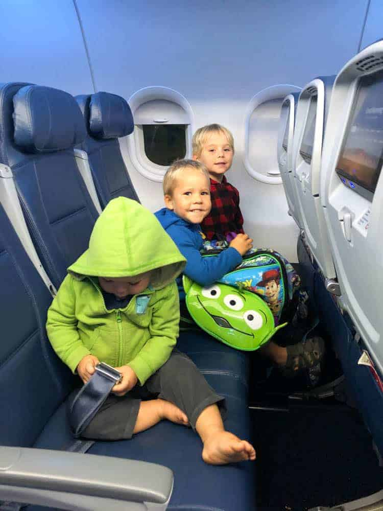 three young boys on an airplane