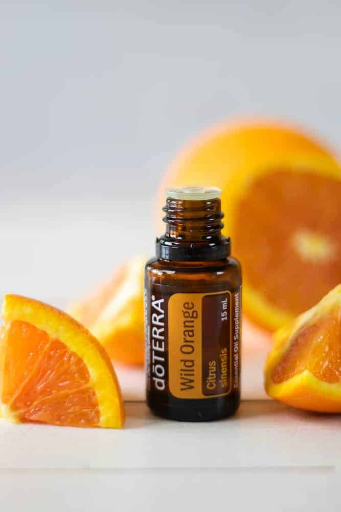 DoTERRA essential oil and orange slices on white backdrop