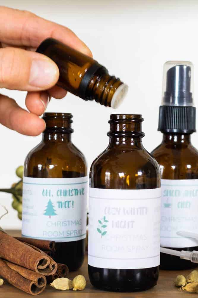 dropping essential oils into a holiday room spray bottle