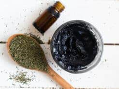 black drawing salve in small mason jar with essential oil bottle and dried herbs ion table