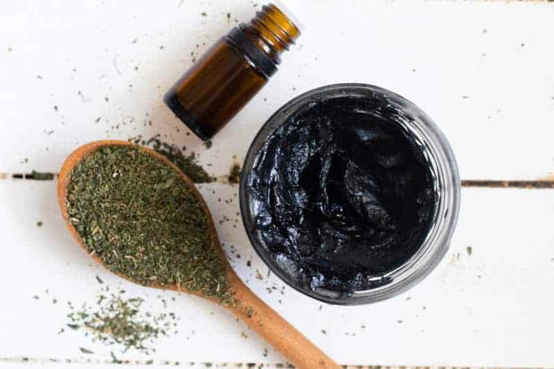black drawing salve in small mason jar with essential oil bottle and dried herbs on table