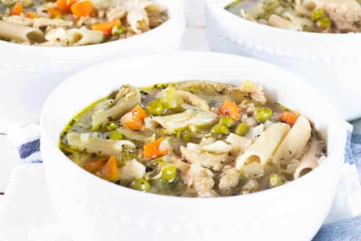 turkey noodle vegetable soup in white bowls