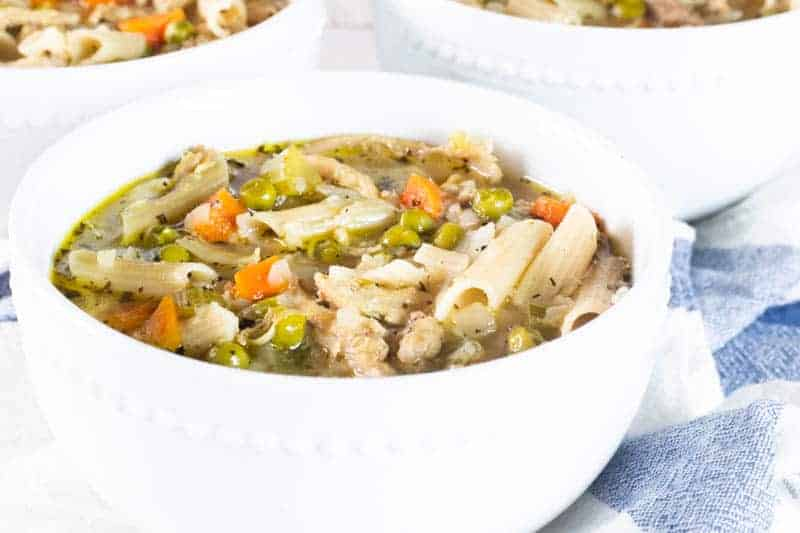 turkey soup with noodles and vegetables in white bowl