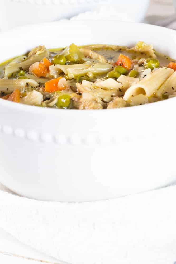 white bowl full of turkey noodle soup