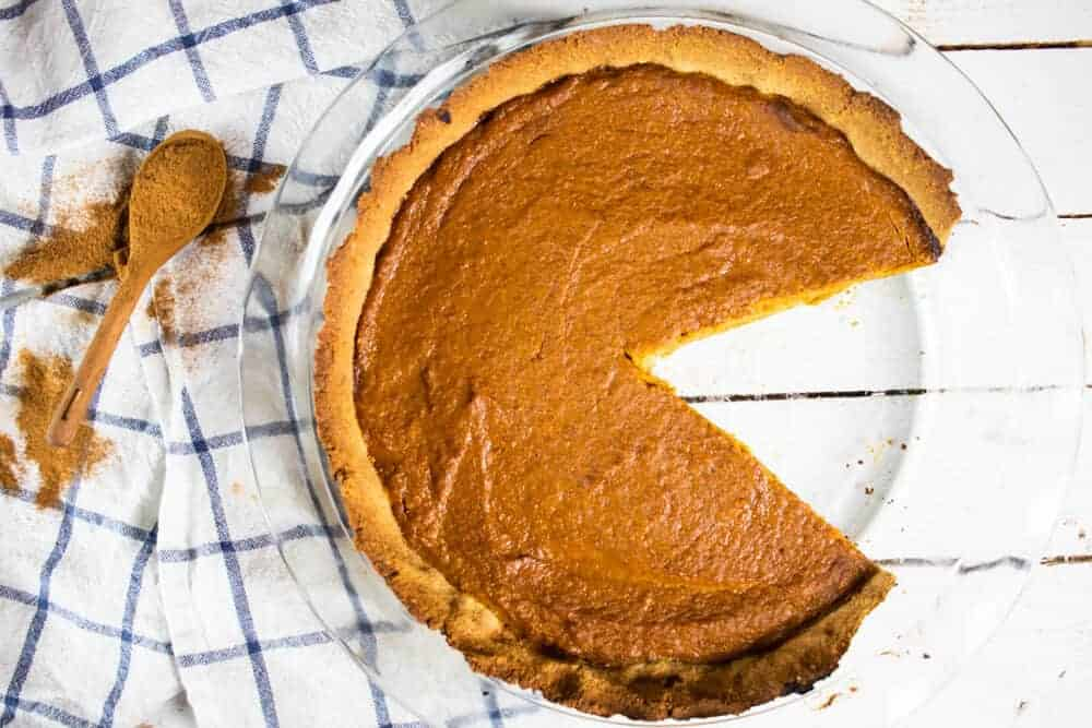 pumpkin pie with slice cut out of it on blue and white stripe tea towel