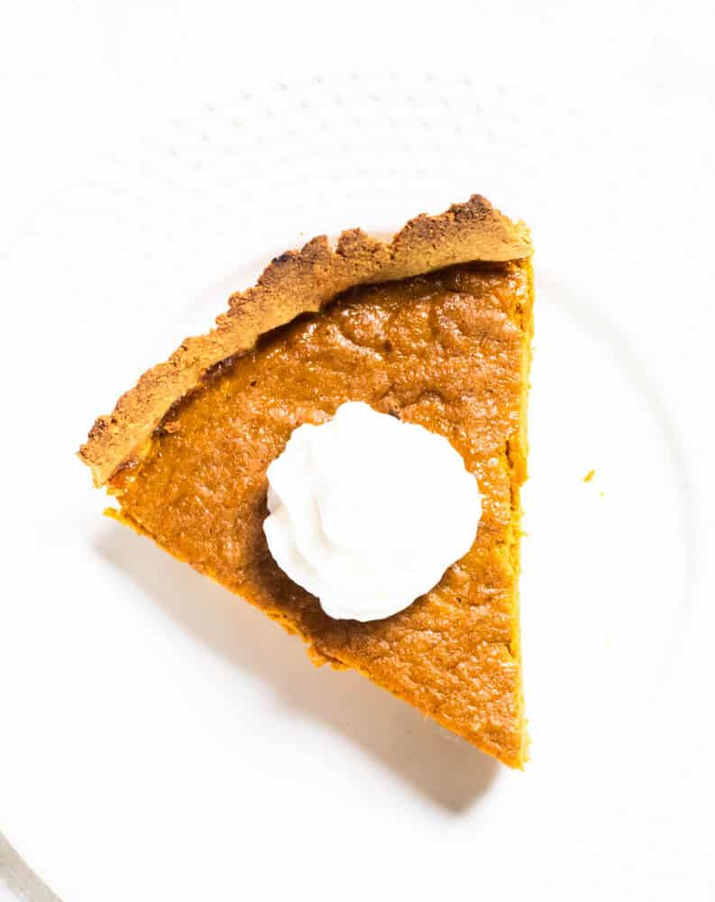 slice of pumpkin pie with whipped cream on white plate and a gluten free crust