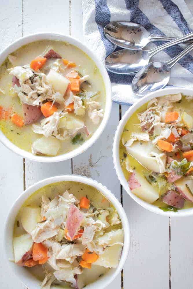 bowls of whole30 chicken vegetable soup on white shiplap