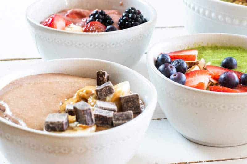 Two berry smoothie bowls and one chocolate with toppings in white bowls on white shiplap table