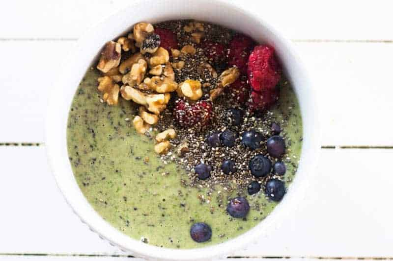green smoothie bowl with fresh fruit and chopped nut toppings